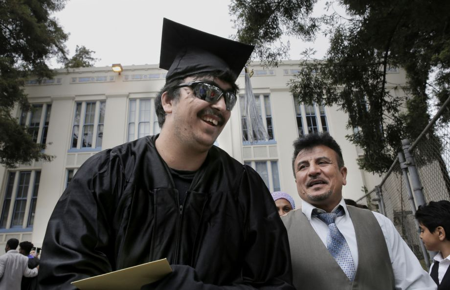 Saleh Khalaf and father Raheem smile after Wednesday's graduation ceremonies in Oakland.