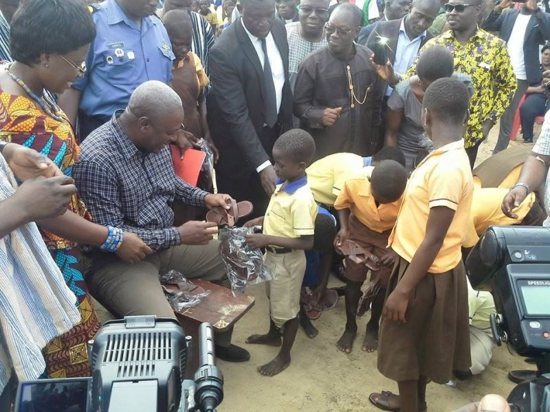 "President Mahama poses for a photo opportunity in the name of free school sandals programme. The programme did not continue after this photo opportunity they christened ""pilot project"""